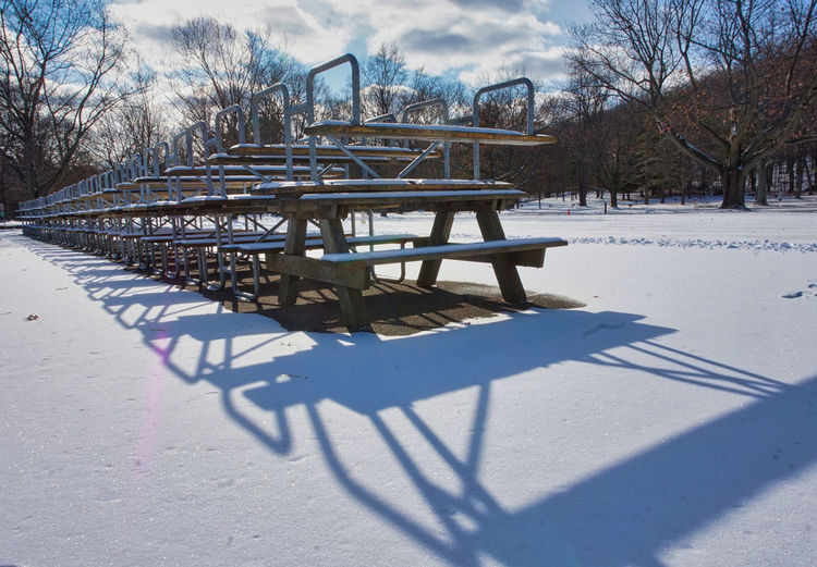 Empty park bench on snow covered field