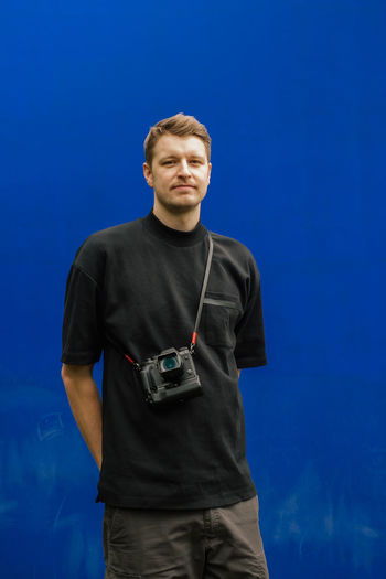 Young man with camera standing against blue background