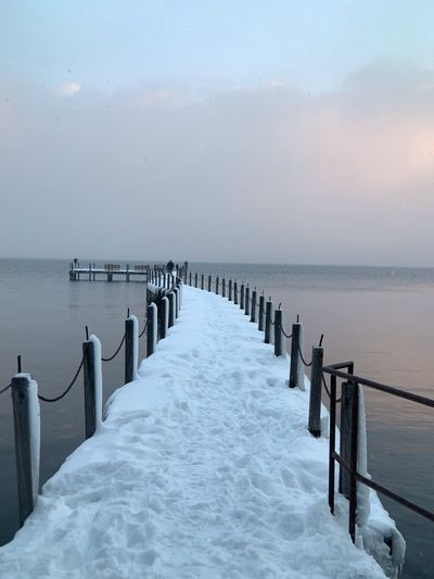 Wooden posts in sea against sky during winter