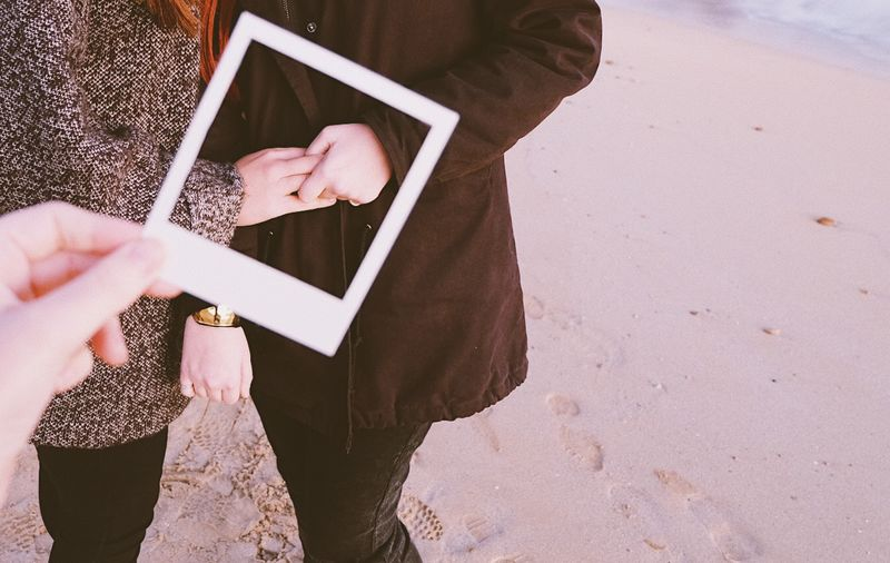 Cropped image of person holding instant transfer print against couple holding hands at beach