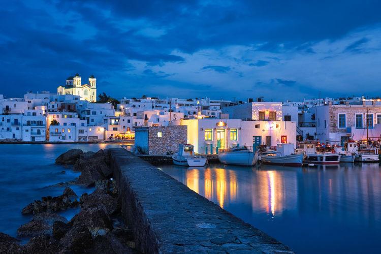 Illuminated city by sea against sky at dusk