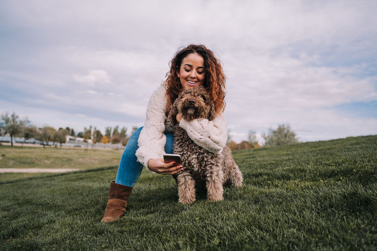 Smiling woman taking selfie with dog against sky