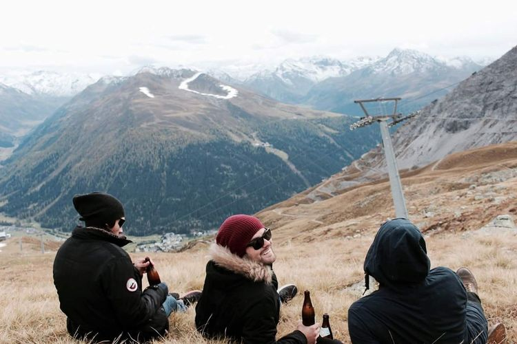 Young men sitting with beer on mountain