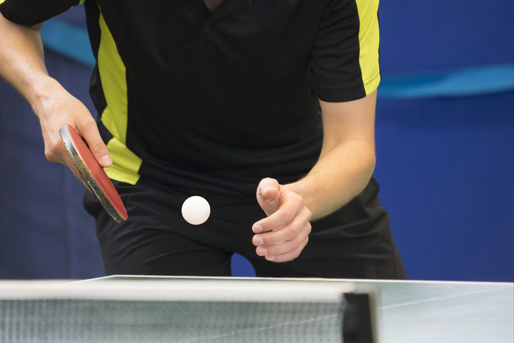 Table Tennis Player serving Casual Clothing Clothing Front View Hand Holding Human Hand Indoors  Lifestyles Men Midsection Occupation One Person Real People Skill  Sport Standing Table Working
