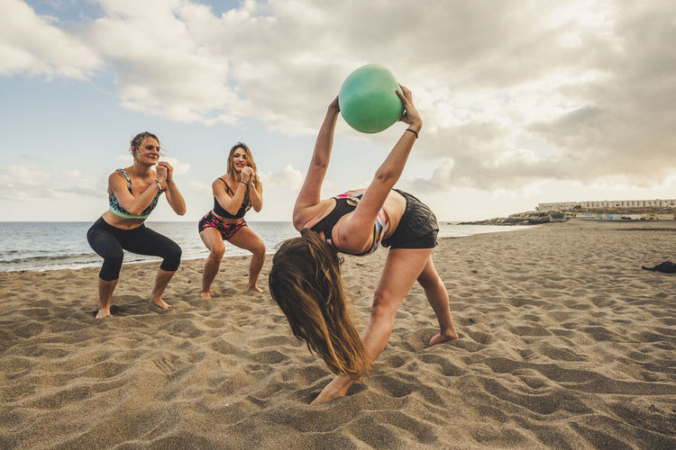 Women exercising on sand against sea at beach