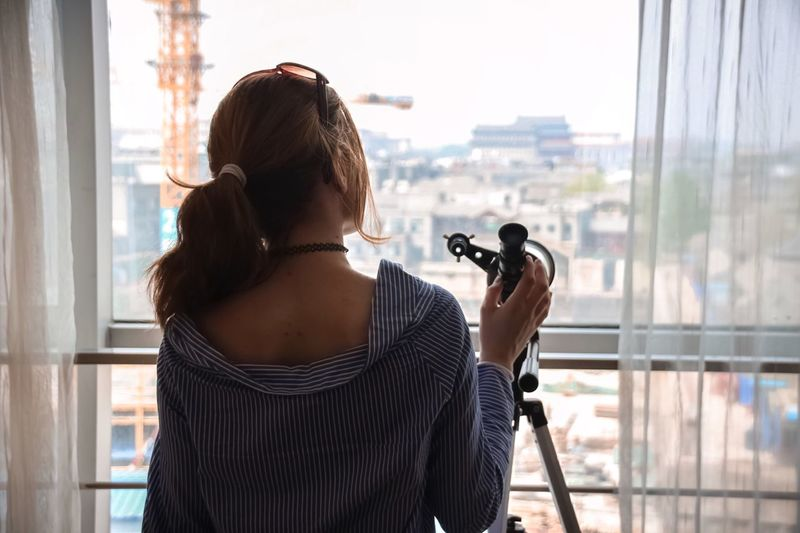 Rear view of woman standing by telescope at home
