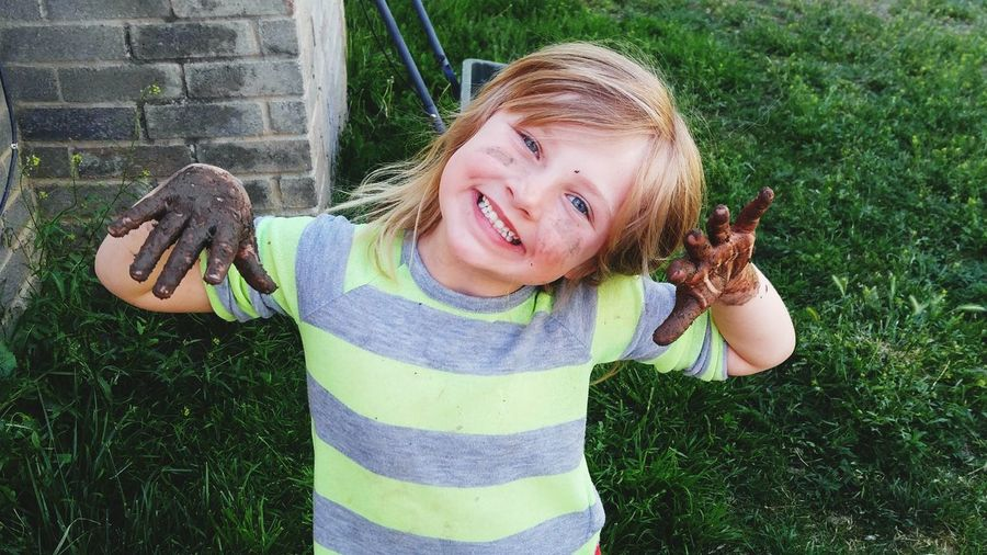 High angle portrait of cute smiling girl with muddy hand standing on grass