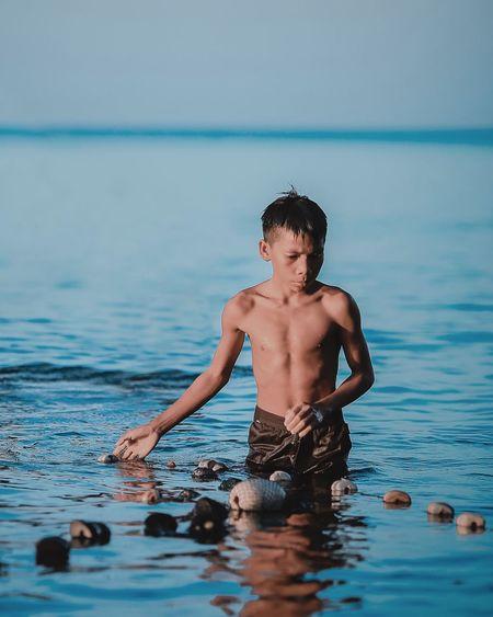 Shirtless man fishing in sea against sky