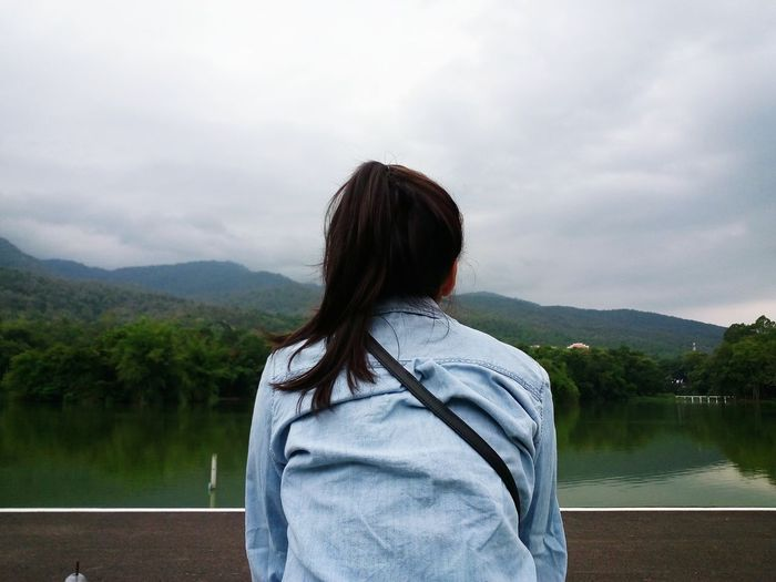 Rear view of woman relaxing against lake and mountains