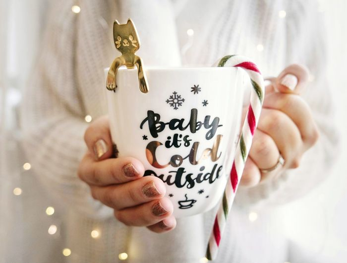 Christmas moment. Hands holding a mug with text baby it's cold outside. Baby It's Cold Outside Teaspoon Tea Cocoa Candy Corn Mug Cup Tea Cup Christmas Lights Lifestyles Sweater Woman EyeEmNewHere Human Hand Fingernail Christmas Celebration Holding Giving Close-up Christmas Decoration Tea - Hot Drink