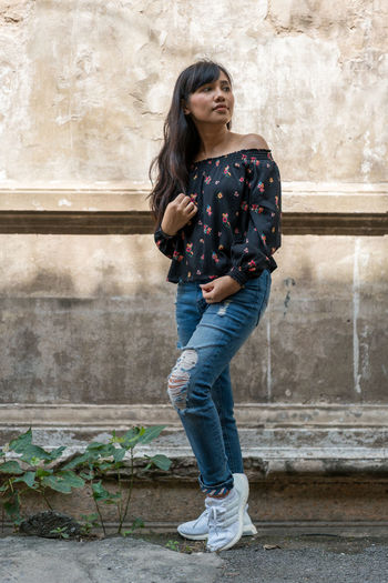 Tanned asian girl wearing jeans looking to the side while standing against a stone wall of an abandoned building in Bangkok, Thailand. Asian  Girl Floral Blouse Thailand Front View Thai Female Tanned Black Floral Pattern Top Shirt Standing Posing Short Casual Clothing Full Length Outdoors Stone Wall Distressed Jeans Brunette Asian Girl Oriental White Sneakers