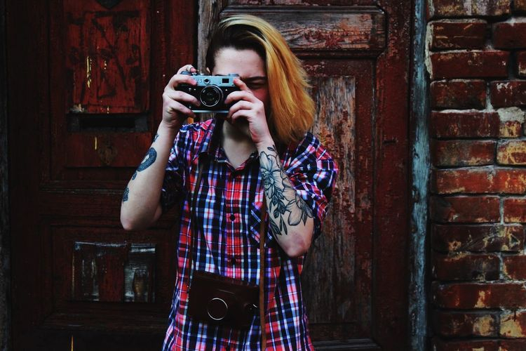 Woman with tattoo photographing through camera against brick wall