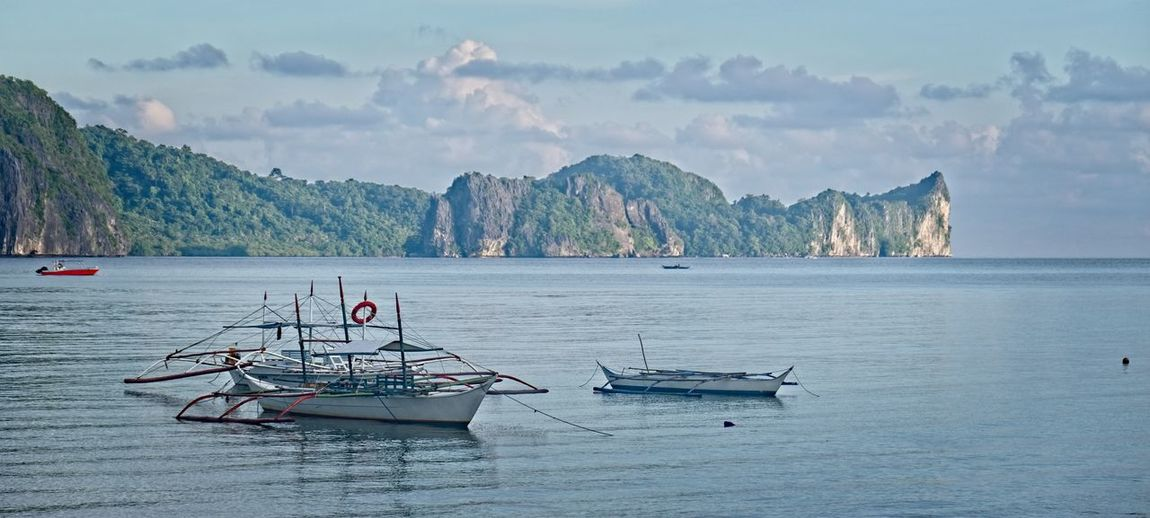 Palawan Philippines Water Nautical Vessel Transportation Mode Of Transportation Mountain Sea Beauty In Nature Sky Scenics - Nature Tranquil Scene Nature Tranquility Waterfront Non-urban Scene No People Day Cloud - Sky Moored Idyllic Outdoors Sailboat Yacht Palawan Philippines Resort Ocean Boat