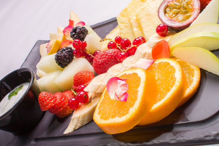 Various Sliced Fruits With Dip Served In Plate