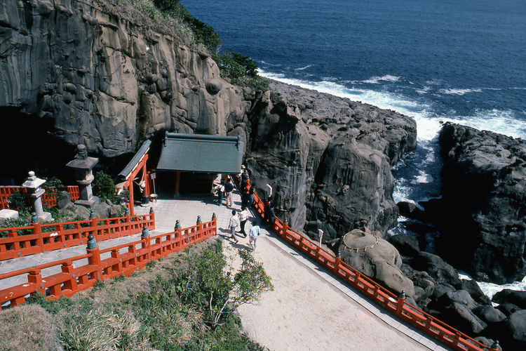 People entering shrine against the sea