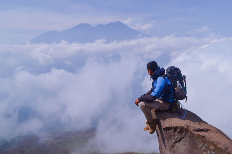 Man sitting on mountain against cloudy sky