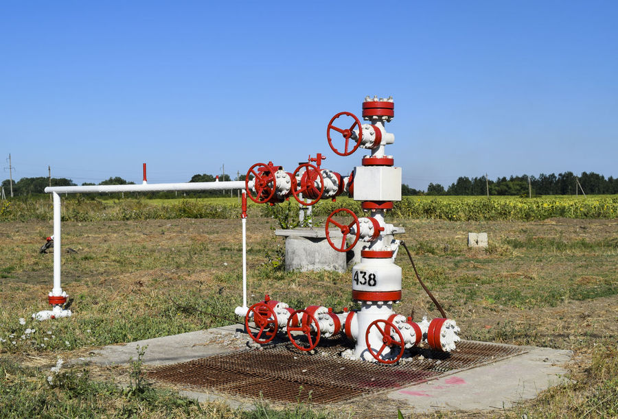 Well for oil and gas production. Oil well wellhead equipment. Oil production. Gas Industrial Industry Valve Clear Sky Day Equipment Field Gasprom Gazprom Grass No People Oil Outdoors Petrol Refinery Rosneft Sky Text Tree Well