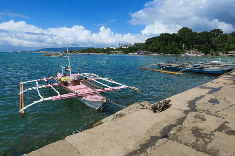 Pink wooden fishing boat docked in a Philippine village Boat Dock Bohol Docked Feminine  Feminism Fisherman Boat Fishermen Boat Fishermen's Life Fishing Boats Fishing Village Girly Harbor View Island Living It's More Fun In The Philippines Moored Boats Nautical Pink Colors Pink Colour Sailor Seafarer Seafaring Tagbilaran Village Photography Wooden Boat
