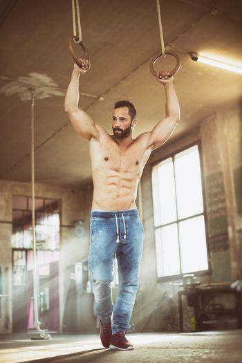 Full Length Of Shirtless Muscular Man Holding Gymnastic Rings