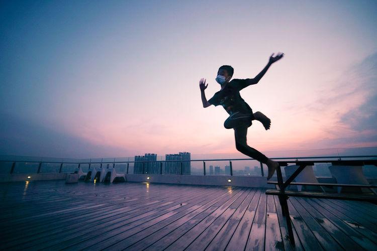 Boy jumping on floor against sky