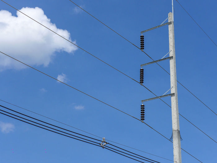 Low angle view of power lines against sky