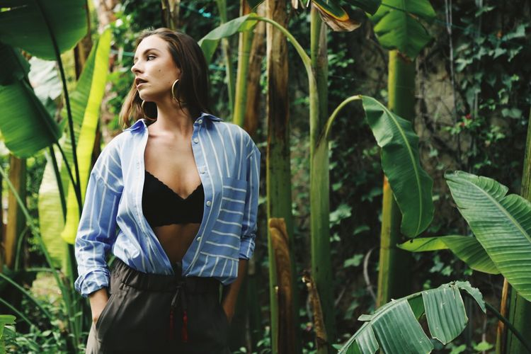Woman wearing open shirt surrounded by banana leafs