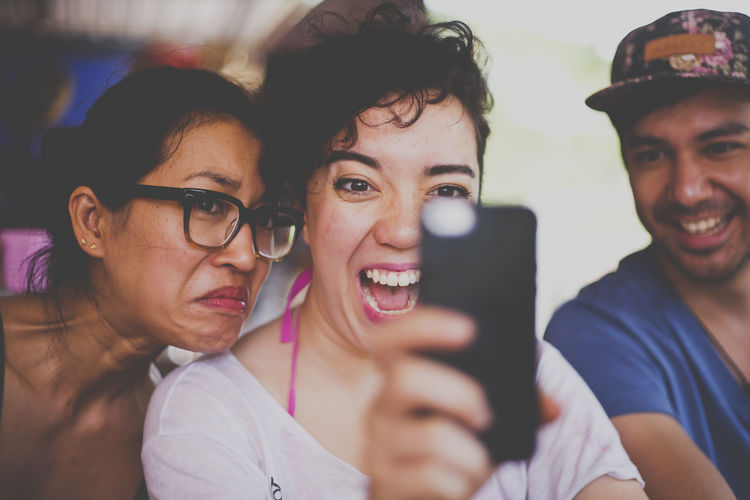 Casual Clothing Celebration Communication Connection Focus On Foreground Friendship Headshot Holding Indoors  Leisure Activity Lifestyles Long Hair Looking At Camera Mobile Phone Person Portrait Smart Phone Togetherness Toothy Smile Wireless Technology Young Adult Young Women