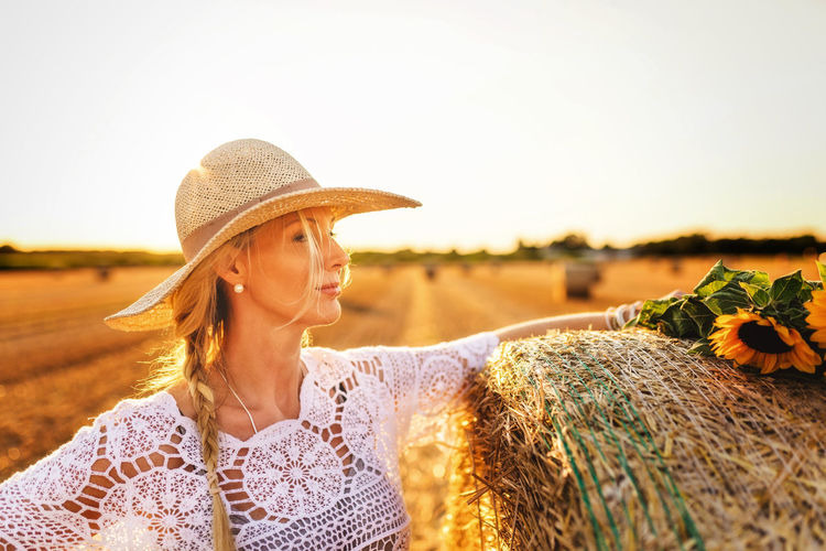 Woman wearing straw hat on a field during sunset