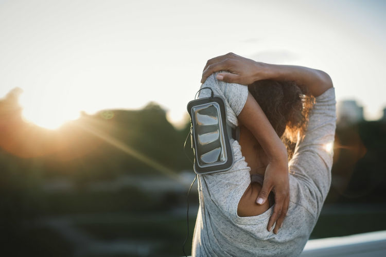 Midsection of woman with arms raised against sky during sunset