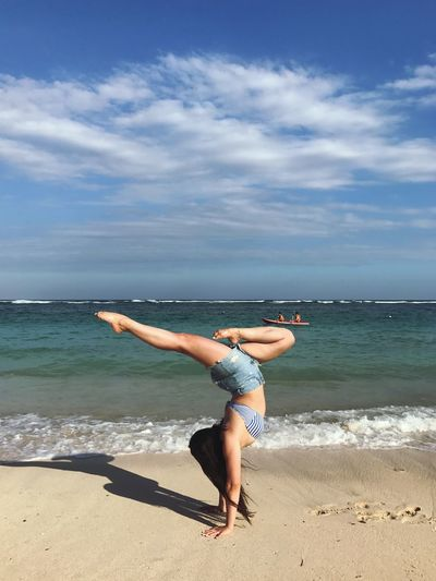 Full length of woman doing handstand on shore at beach against sky