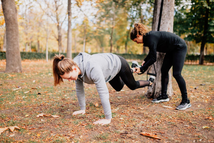 Friends exercising by trees in park during autumn