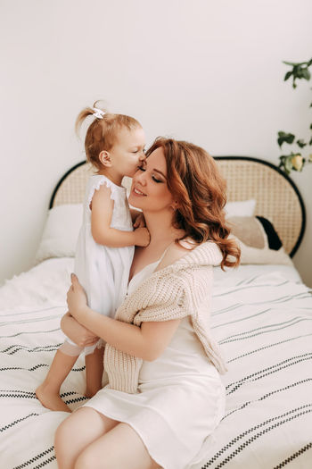 Mother and baby girl sitting on bed at home