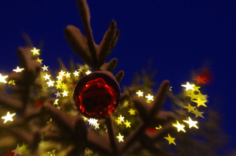Low angle view of illuminated christmas lights against sky at night