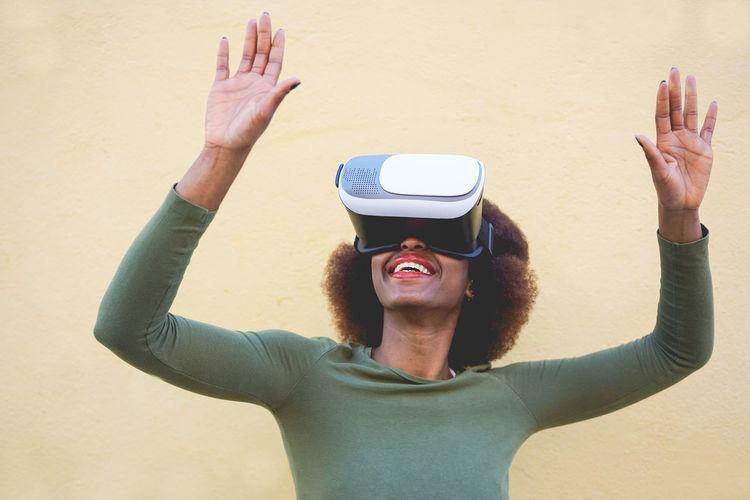 Smiling woman wearing virtual reality simulator against wall