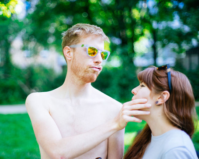 Loving Man Holding Face Of Girlfriend In Park