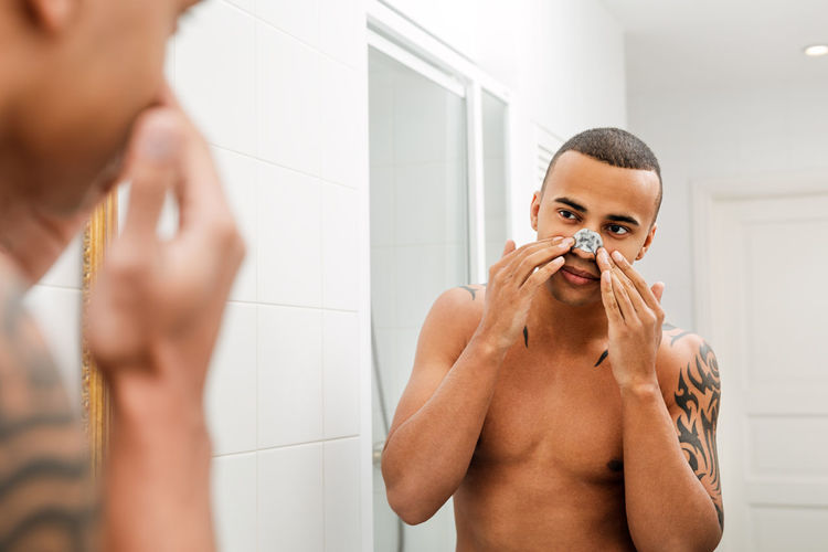 Bathroom Mirror Home One Person Hygiene Lifestyles Indoors  Standing Reflection Body Care Preparation  Applying Shirtless Routine Handsome Males  Looking Masculinity Care Skin Real Natural Cosmetics