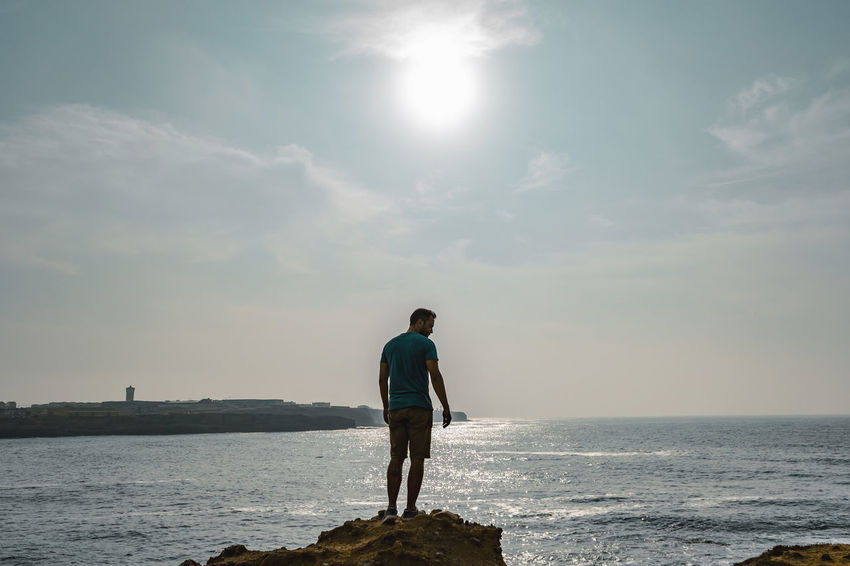Water Sky Sea One Person Real People Scenics - Nature Beauty In Nature Lifestyles Rear View Full Length Men Standing Leisure Activity Nature Sunlight Land Day Horizon Horizon Over Water Outdoors Lens Flare