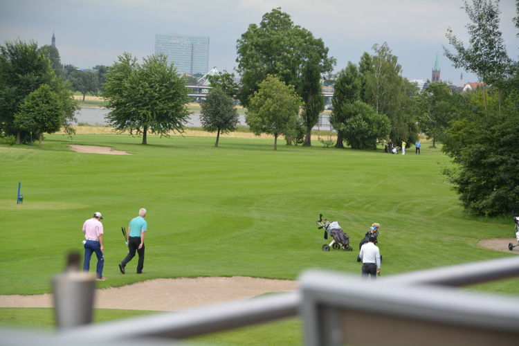 People at golf course against trees