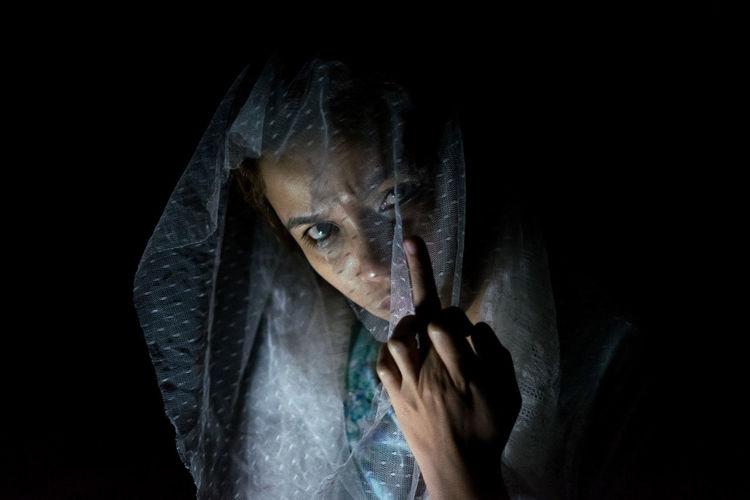 Close-up portrait of a woman against black background