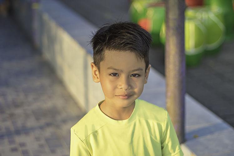 Portrait of boy on footpath in city