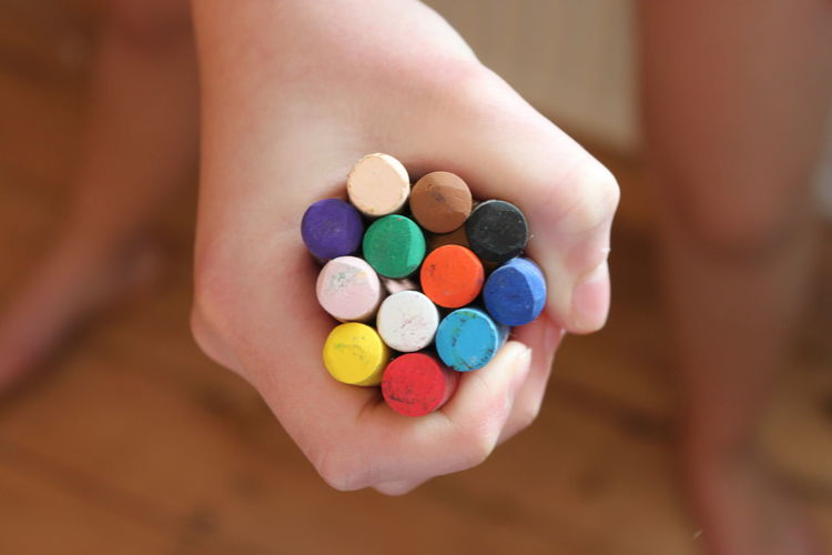 Cropped hand of child holding colorful crayons