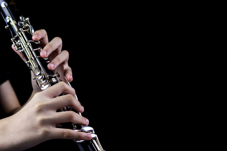 Music Instrument Clarinet Player, Clarinet Player Isolated on black Music Arts Culture And Entertainment Musical Instrument Holding Artist One Person Human Hand Indoors  Studio Shot Hand Black Background Musician Human Body Part Performance Playing Skill  Real People Wind Instrument Copy Space Finger