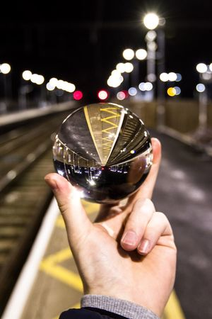 Lens Ball Circle Ball Glass Ball Train Station Train Tracks Way2ill London London_only Createcommune Create Creative Photography City Street City Life Cityscape Ball Photography Lens Ball Crystal Ball Human Hand Human Body Part Real People Holding Focus On Foreground One Person Personal Perspective Transportation Close-up Illuminated Outdoors Night City