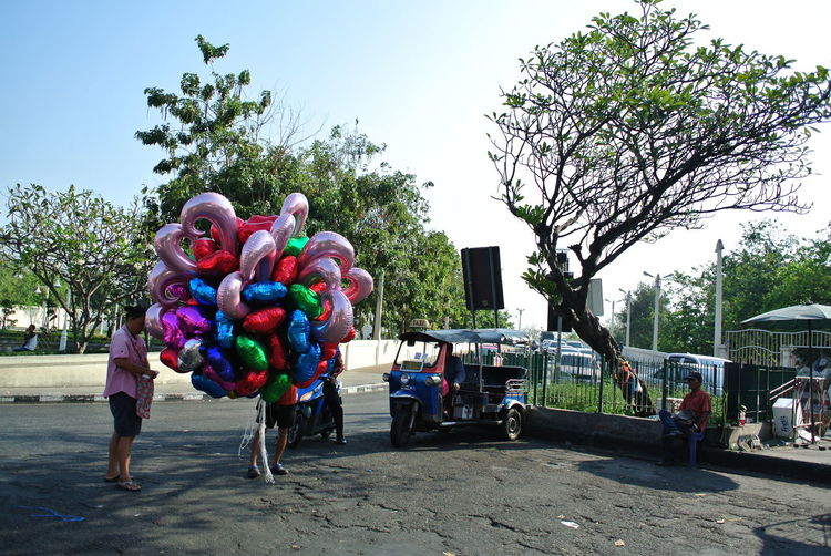 Valentine balloon seller on Valentine day Ballon, Car Men Outdoors Parking Street Streetlife Streetphotography Tree Tuk Tuk Valentine Balloon Street Photography Bangkok Spotted In Thailand