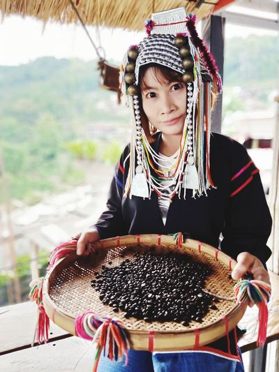 Portrait of woman holding basket with roasted coffee beans