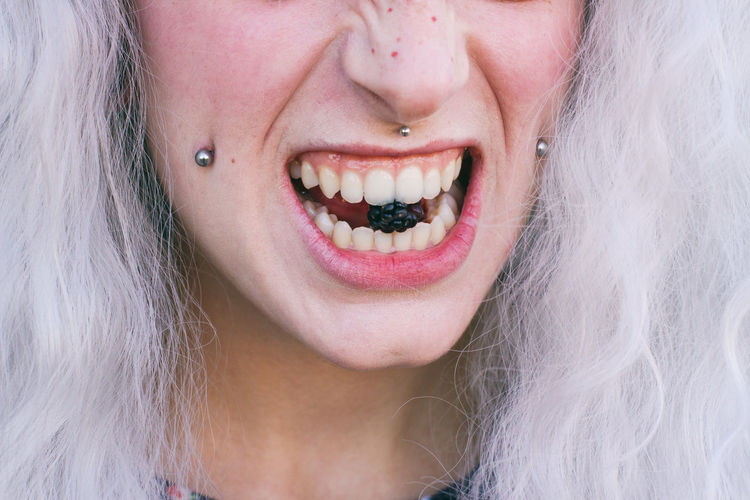 Cropped image of female model eating blackberry