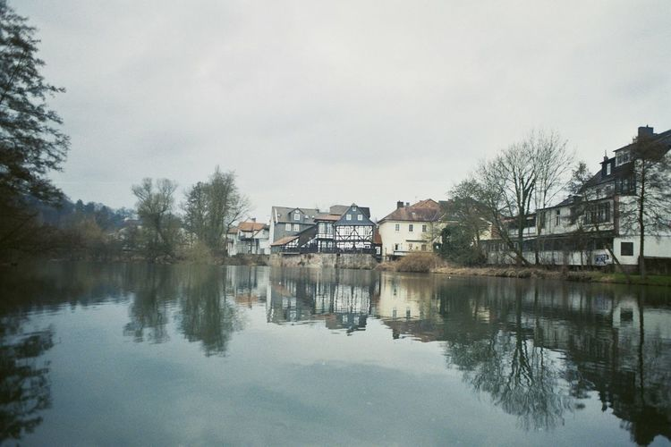 Reflection Of Houses And Trees In Calm Lake