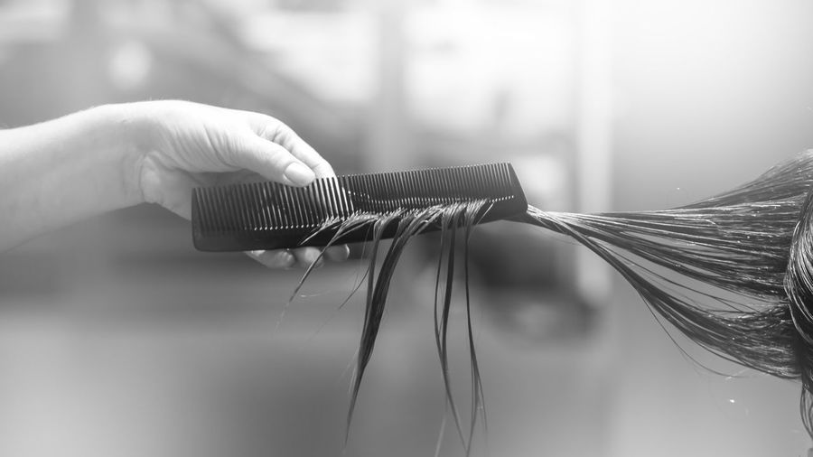 Cropped hand combing hair