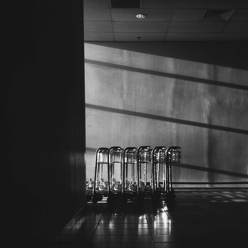 Empty luggage carts arranged by wall