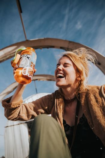 Hydration Station Joshua Tree, CA Lifestyles Happiness Holding Smiling Real People Emotion Young Adult Leisure Activity Women Portrait Front View Mouth Open Outdoors Headshot Low Angle View